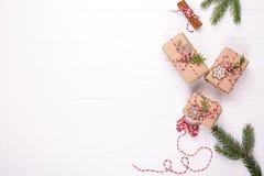 De giften van verpakkingskerstmis De vakjes van de de vakantiegift van de Ecoambacht met rood en wit koord, decoratie, pijnboom w stock foto's