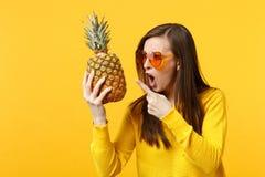 De gillende jonge vrouw die in hartglazen wijsvinger op vers rijp ananasfruit richten isoleerde op geeloranje stock foto's
