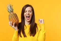 De gillende jonge vrouw die ogen houden sloot het doen van fruit van de de greep het verse rijpe die ananas van het winnaargebaar royalty-vrije stock afbeeldingen