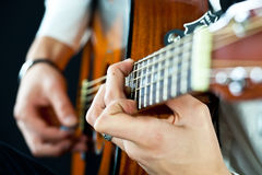 De gitaar in de handen van de gitarist stock afbeelding