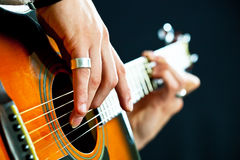 De gitaar in de handen van de gitarist stock fotografie