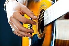 De gitaar in de handen van de gitarist royalty-vrije stock foto's