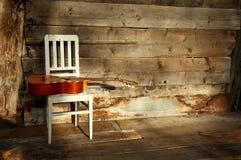 De gitaar van blauw op een witte stoel met een houten backgr Stock Fotografie