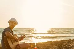 De gitaar van het jonge mensenspel op het strand en geniet van in zonsondergang royalty-vrije stock foto