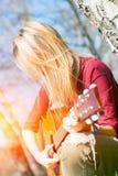 De gitaar van meisjesspelen stock afbeelding