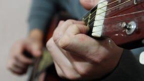 De gitaar van mensenspelen, zijn vingers stock footage