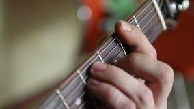 De gitaar van mensenspelen, zijn vingers op fretboard stock videobeelden