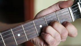 De gitaar van mensenspelen, zijn vingers op fretboard stock video