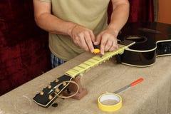 De gitaarreparatie en dienst - Arbeidersvoorbereiding het kleven van lijstwerken royalty-vrije stock fotografie