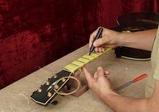 De gitaarreparatie en dienst - Arbeidersvoorbereiding van lijstwerken voor grijns stock afbeeldingen