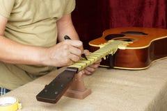 De gitaarreparatie en dienst - Arbeidersvoorbereiding van lijstwerken voor grijns royalty-vrije stock afbeelding