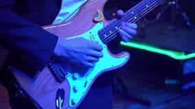 De gitaarspeler is zeer actief op stadium met zijn popgroep Close-up stock footage