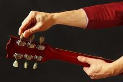De gitarist stemt de gitaar op donkere achtergrond royalty-vrije stock afbeeldingen