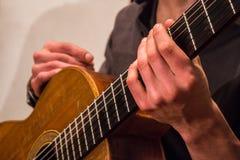 De gitarist van het gemengde behoren tot een bepaald ras houdt een oude met de hand gemaakte klassieke gitaar stock foto