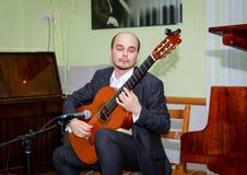 De gitarist voert een muziekstuk uit en zet zijn ziel in het royalty-vrije stock foto's