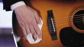 De gitarist wrijft de gitaar witte doek van stof stock footage