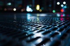 De glanzende natte rooster van het straatriool bij nacht stock afbeeldingen