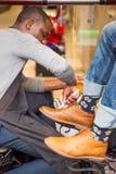 De glanzende schoenen van de schoenshiner stock afbeeldingen