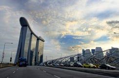 De glasbouw en auto's op weg in Singapore Stock Afbeelding