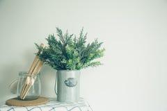 De glaskom met een houten lepel, zette een valse boom in de kleine blikken, oude keuken Stock Foto's