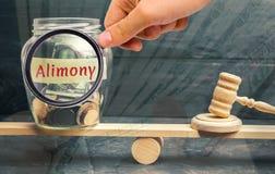 De glaskruik en de inschrijving 'Alimentatie 'en de hamer van de rechter zijn op de schalen Betaling van alimentatie van één van  royalty-vrije stock afbeelding