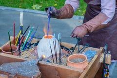 De glaskunstenaar in zijn workshop maakt gekleurde glasparel stock foto