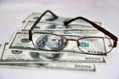 De glazen in een kader liggen op dollars op een witte lijst uit worden uitgespreid die stock foto's