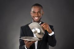De Glazen kap van kelnersserving meal in royalty-vrije stock afbeeldingen
