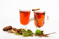 De glazen met overwogen wijn of hete drank dichtbij de herfstbladeren en de koekjes op witte achtergrond, sluiten omhoog Overwoge Royalty-vrije Stock Foto's