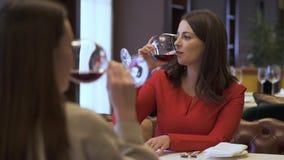 De glazen van damegerinkels rode wijn in het restaurant Het mooie meisje met lang haar die in het restaurant, dame rusten is stock video