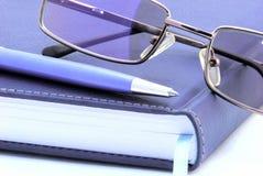De glazen van de agenda, van de pen en van de lezing over wit Stock Foto's