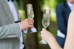 De glazen van de de holdingschampagne van de bruid en van de bruidegom Stock Foto's