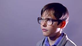 De glazen van de het portretschooljongen van de jongens nerd tiener op purper onderwijs als achtergrond stock video