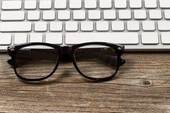 De glazen van de Hipsterlezing met toetsenbord op rustieke houten Desktop Stock Foto's