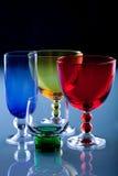 De glazen van de kleur op de blauwe glaslijst Royalty-vrije Stock Foto's