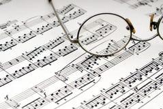 De glazen van de lezing op bladmuziek Stock Foto's