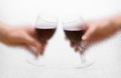 De glazen van de wijn in de handen Stock Afbeelding