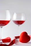 De glazen van de wijn en een hart Stock Foto's