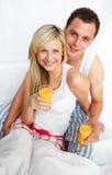 De glazen van het de holdingsjus d'orange van het paar in bed Stock Foto