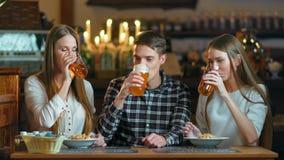 De glazen van het vriendengerinkel van bierclose-up op de achtergrond van de bar stock footage