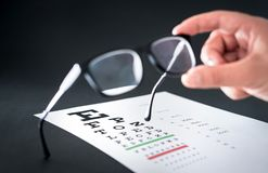 De glazen van de opticienholding De grafiek van de zichttest op de achtergrond stock afbeeldingen