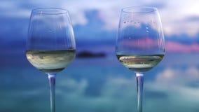De glazen witte wijn bevinden zich naast oneindigheids zwembad door zonsondergangmening te verbazen Langzame Motie 3840x2160 stock footage