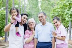De glimlach van de drie generatiefamilie bij de camera stock afbeeldingen