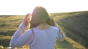 De glimlachemoties van het meisjesportret in de stralen van het zonsondergangzonlicht Aard hils en gebied stock video