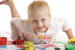 De glimlachen van het kind gelukkig tijdens het schilderen zitting Stock Afbeeldingen
