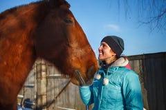 De glimlachen van het roodharigemeisje bij rood paard op een zonnige de winterdag royalty-vrije stock afbeelding