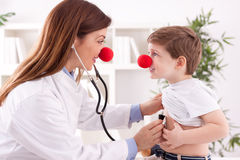 De glimlachende aanbiddelijke vrouwelijke artsenclown luistert geduldig hart Royalty-vrije Stock Foto's