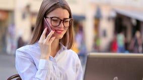 De glimlachende aantrekkelijke dame met rode lippen spreekt op haar cel telefoon en het gebruiken van haar laptop stock footage