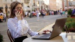 De glimlachende aantrekkelijke dame met rode lippen spreekt op haar cel telefoon en het gebruiken van haar laptop stock video