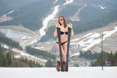 De glimlachende actieve sexy vrouw bevindt zich op de bovenkant van de helling met skis Het dragen van zwempak, laarzen en zonneb Royalty-vrije Stock Foto's